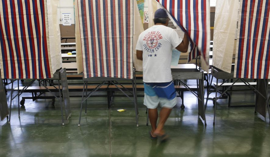 FILE - In this Saturday, Aug. 13, 2016 file photo, a voter enters a both at a polling place during the Hawaii primary at Kawananakoa Middle School, in Honolulu. A federal appeals court Monday, Aug. 15, 2016, upheld an earlier decision to support the way Hawaii holds its primary elections, rejecting the Democratic Party's desire to exclude non-Democrats from advancing candidates to the general election. (AP Photo/Marco Garcia, File)