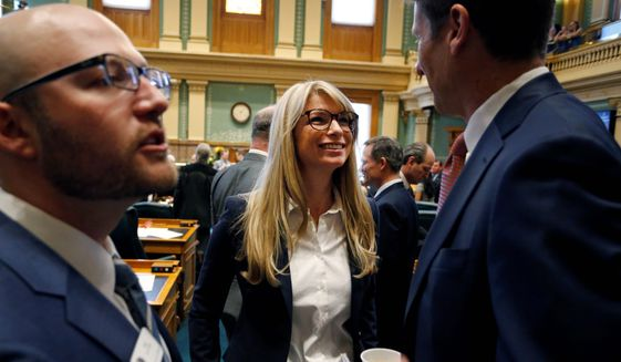 Colorado Rep. Brittany Pettersen (center) speaks with House Democrats' Chief of Staff Ian Silverii (left) and a visitor on the opening day of the Colorado legislative session in Denver this year. (Associated Press)