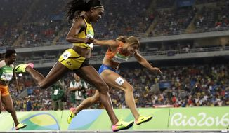 Elaine Thompson, left, from Jamaica crosses the line to win the gold medal in the women's 200-meter final during the athletics competitions of the 2016 Summer Olympics at the Olympic stadium in Rio de Janeiro, Brazil, Wednesday, Aug. 17, 2016. (AP Photo/Matt Dunham)