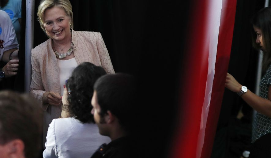 Democratic presidential candidate Hillary Clinton pauses for a photo as a staff member watches at right from behind an American flag as Clinton leaves a campaign event at John Marshall High School in Cleveland, Wednesday, Aug. 17, 2016. (AP Photo/Carolyn Kaster)