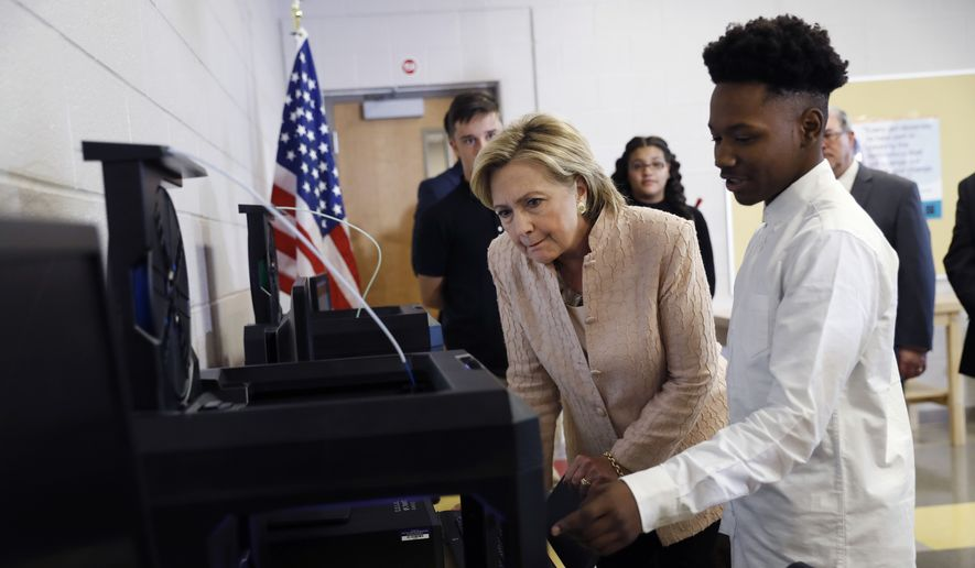Democratic presidential candidate Hillary Clinton looks at a 3D printer with a student as she tours classrooms at John Marshall High School in Cleveland, Wednesday, Aug. 17, 2016, before participating in a campaign event. (AP Photo/Carolyn Kaster)