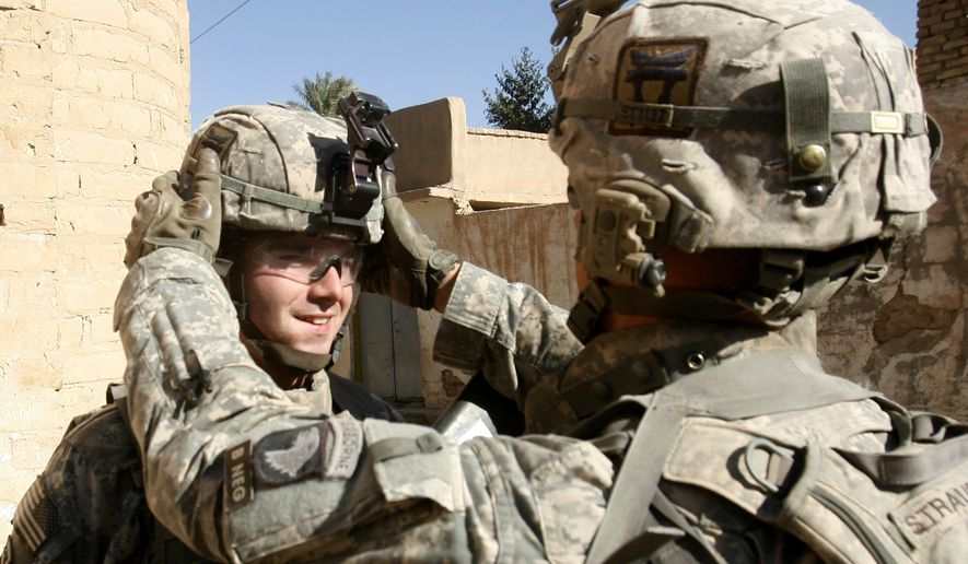 A U.S. soldier adjusts his colleague's helmet during a patrol mission in the town of Youssifiyah, Iraq. (Associated Press)