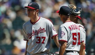 Washington Nationals starting pitcher Stephen Strasburg, left, confers with pitching coach Mike Maddux, center, and catcher Wilson Ramos after Strasburg gave up an RBI-single to Colorado Rockies' Nolan Arenado in the first inning of a baseball game Wednesday, Aug. 17, 2016 in Denver. (AP Photo/David Zalubowski)