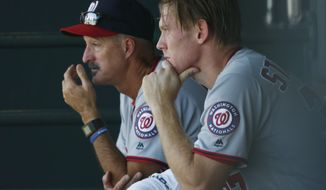 Washington Nationals starting pitcher Stephen Strasburg, right, sits with pitching coach Mike Maddux after Strasburg faced 11 batters before retiring the Colorado Rockies in the first inning of a baseball game Wednesday, Aug. 17, 2016 in Denver. (AP Photo/David Zalubowski)