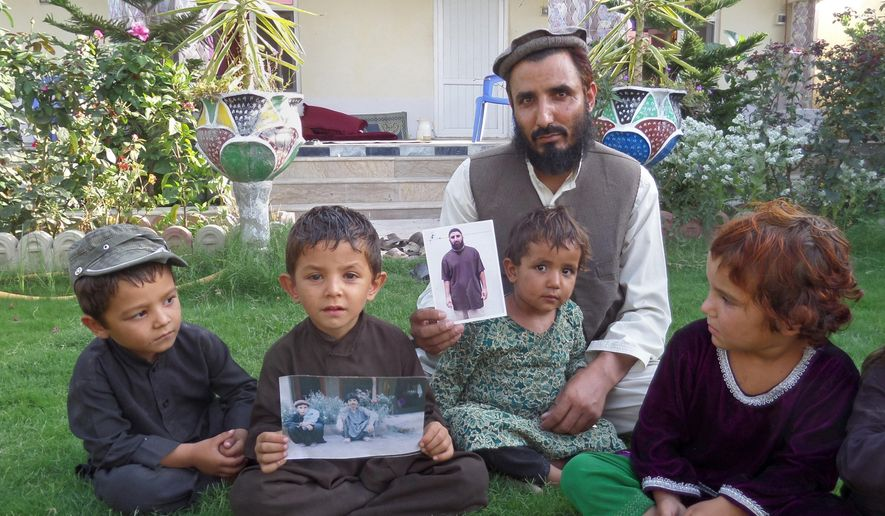 """In this Tuesday, Aug. 16, 2016, photo, Fazel Karim, holds a picture of his brother, who was recently released from the Guantanamo Bay detention center, at his home in the village of Haiderkhil, Mandozai district of Khost province, Afghanistan. Obiadullah's family said they're excited their son is among 15 prisoners released from Guantanamo and transferred to the United Arab Emirates this week. They say Obiadullah is now """"free"""" after 14 years in the U.S. prison in Cuba and that they can hardly wait to hear from him. (AP Photo/Nishanuddin Khan)"""