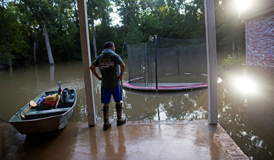 David Key, an insurance adjuster, examines the flood damage to his own backyard in Prairieville, Louisiana. After a series of storms dumped nearly 3 feet of rain on the area, Mr. Key fled with his wife and three children.. (Associated Press)