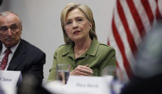 Democratic presidential candidate Hillary Clinton, joined by New York Police Department Commissioner Bill Bratton (left) and others, meets Thursday with law enforcement leaders at John Jay College of Criminal Justice in New York. (Associated Press)