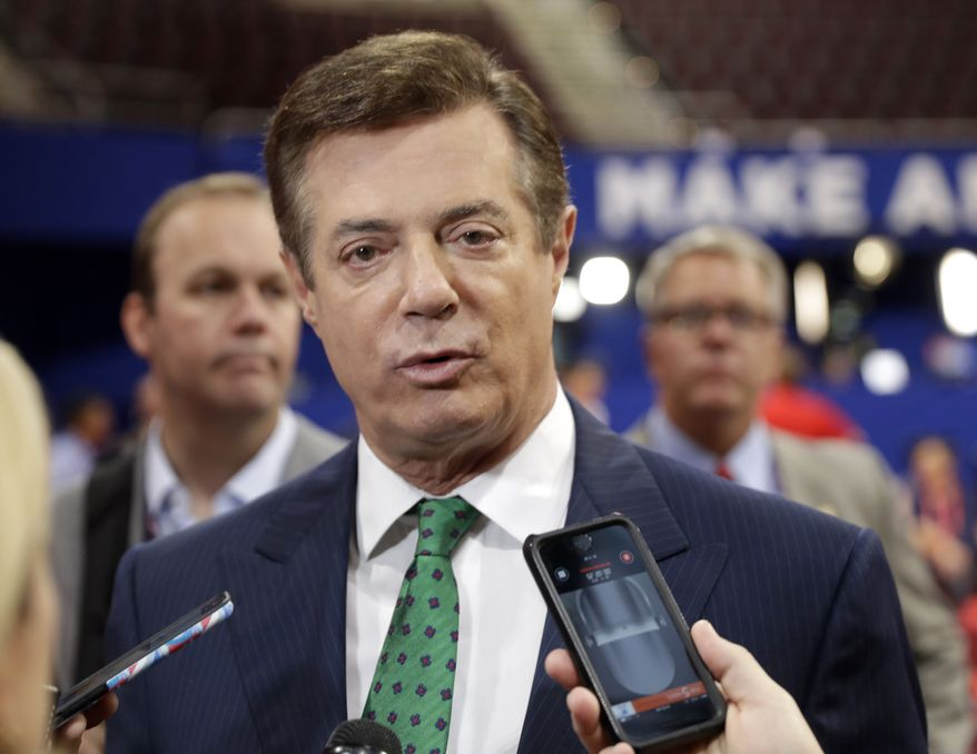 Then-Trump campaign chairman Paul Manafort talks to reporters on the floor of the Republican National Convention at Quicken Loans Arena in Cleveland on July 17, 2016, as Rick Gates listens at back left. (Associated Press) **FILE**