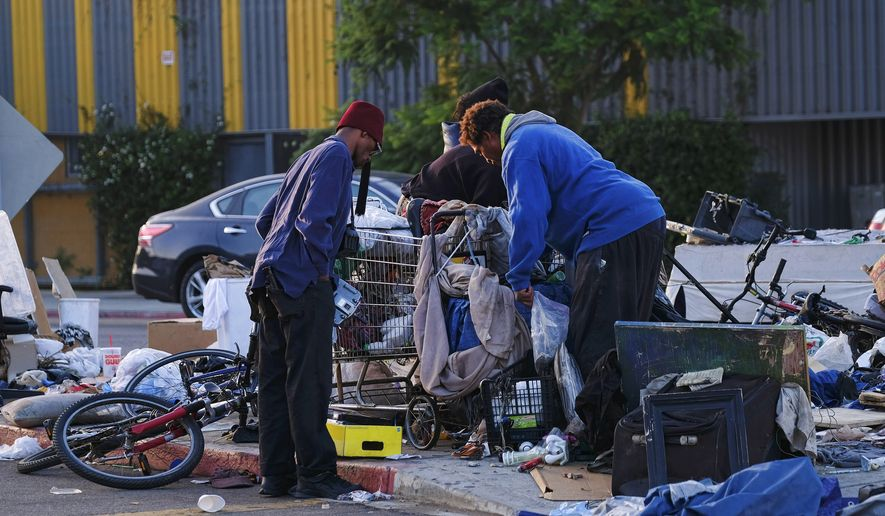 Homeless men sort through their belongings on a traffic island near downtown Los Angeles on Thursday, Aug. 18, 2016. With two weeks left in the state legislative session, county officials from across California continued Wednesday to press Gov. Jerry Brown to declare homelessness a state of emergency. (AP Photo/Richard Vogel)