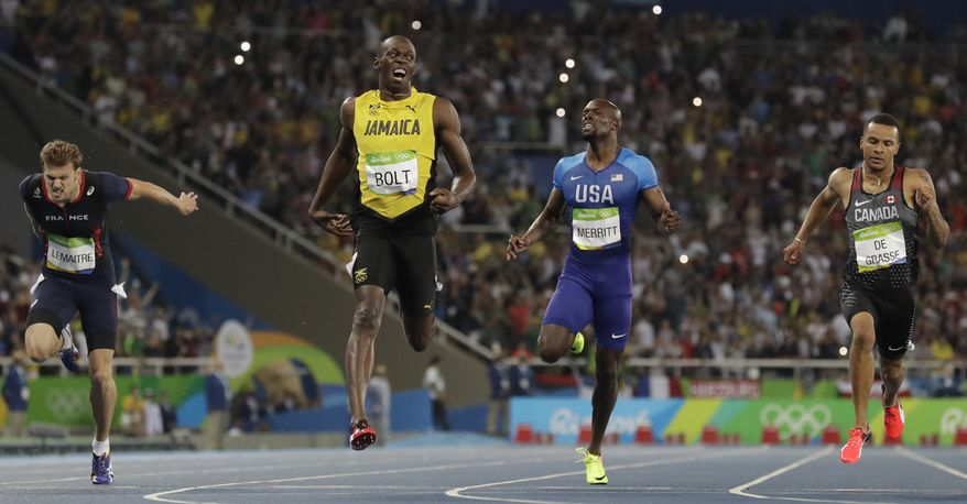 Usain Bolt from Jamaica, second left, crosses the line to win the gold medal in the men's 200-meter final ahead of second placed Canada's Andre De Grasse, right, and third placed France's Christophe Lemaitre, left, during the athletics competitions of the 2016 Summer Olympics at the Olympic stadium in Rio de Janeiro, Brazil, Thursday, Aug. 18, 2016. (AP Photo/David J. Phillip)