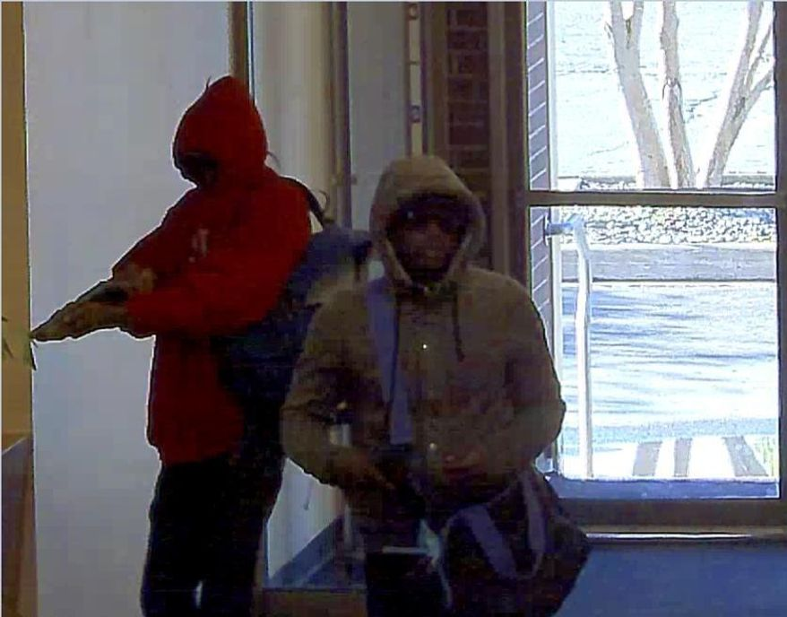 In this Thursday, Aug. 18, 2016, WellsFargo Bank security camera image released by the FBI shows two armed men robbing a bank Thursday morning on Anchorage's east side. One man was armed with a shotgun and the other with a handgun. The men at 10:14 a.m. entered the Wells Fargo Bank at 630 E. Fifth Avenue and demanded money.They carried off cash in a duffel bag with purple straps and left on foot. Witnesses say both were African-American and both wore sunglasses. One wore a red sweat shirt. The other wore a gray sweat shirt and red shoes. ( WellsFargo/FBI via AP)