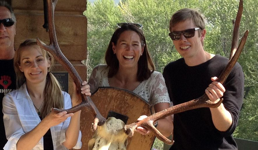 TAKES OUT REFERENCE TO ASSISTANT REGIONAL  LIBRARIAN - Anita Thompson, left, is joined by Library Executive Director Jenny Emery Davidson, middle, and Program Manager Scott Burton as they pose with trophy antlers while returning them to the former home of writer Ernest Hemingway Aug. 5, 2016, in Ketchum, Idaho. Gonzo journalist Hunter S. Thompson so admired the set of trophy elk antlers when he visited the central Idaho home of Hemingway, that he stole them. More than half a century later, The Community Library has returned the antlers.(Christina Jensen/The Community Library via AP)