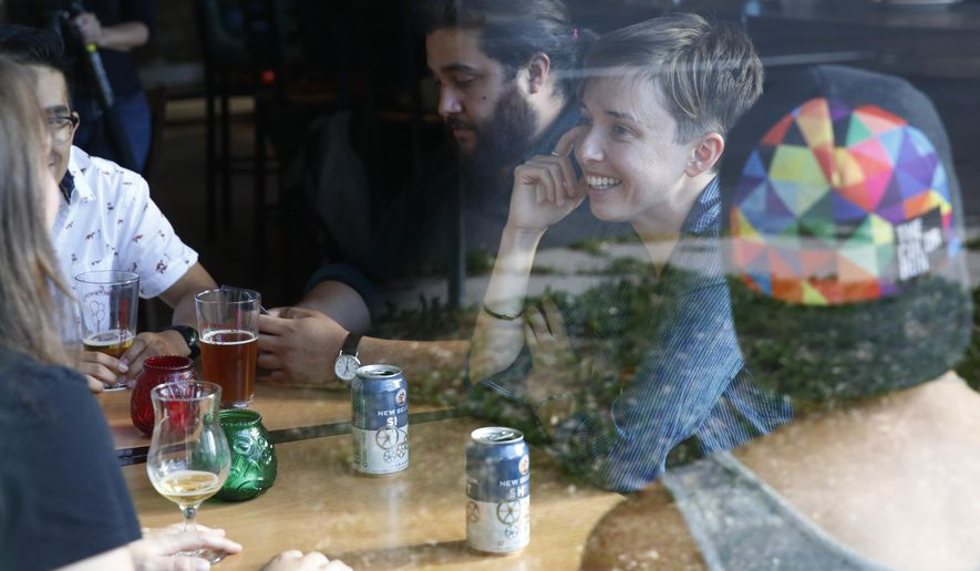 "Diana Downard, 26, a Bernie Sanders supporter who now says she will vote for Hillary Clinton, has drinks with friends at a pub in Denver on July 6, 2016. ""Millennials have been described as apathetic, but they're absolutely not,"" says Downard ""Millennials have a very nuanced understanding of the political world."" (AP Photo/Brennan Linsley)"