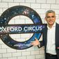 Mayor of London Sadiq Khan poses in front of a new Night Tube logo at Oxford Circus underground station, in London Thursday Aug. 18, 2016. London's mayor says the city has meticulously planned the introduction of limited overnight services on the subway,  services that the city hopes will offer a boost to the local economy. The British capital is unveiling the weekend service Friday,  three years after it was first proposed.  (Dominic Lipinski/PA via AP)