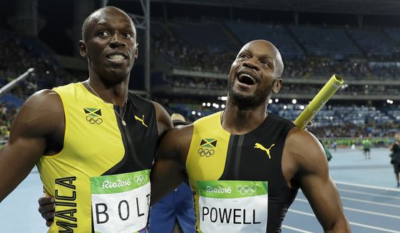 Jamaica's Usain Bolt and Asafa Powell celebrate winning gold in the men's 4 x 100-meter relay final, during the athletics competitions of the 2016 Summer Olympics at the Olympic stadium in Rio de Janeiro, Brazil, Friday, Aug. 19, 2016. (AP Photo/Matt Slocum)