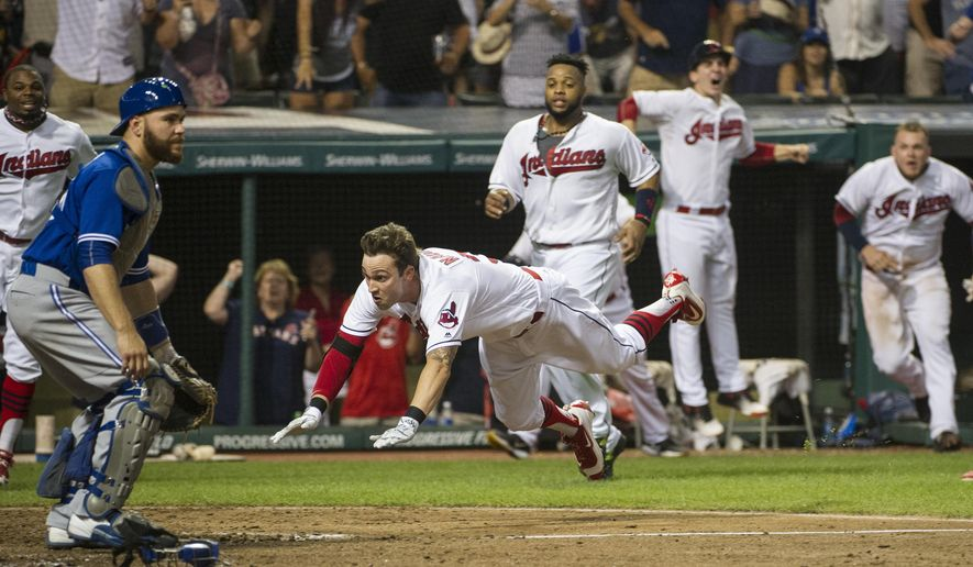 Cleveland Indians' Tyler Naquin, dives for home plate for an inside-the-park home run off Toronto Blue Jays relief pitcher Roberto Osnuo, for the game-winning run in a baseball game in Cleveland, Friday, Aug. 19, 2016. Blue Jays catcher Russell Martin waits for the throw. The Indians won 3-2. (AP Photo/Phil Long)