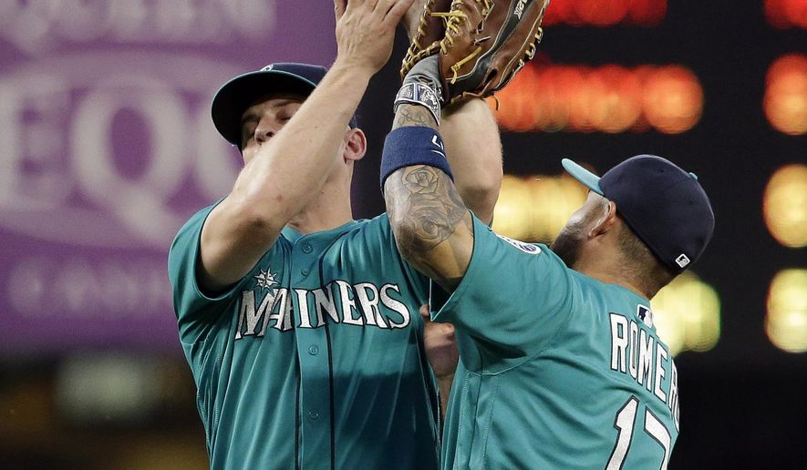 Seattle Mariners third baseman Kyle Seager, left, and first baseman Stefen Romero collide as Seager catches a pop-up from Milwaukee Brewers' Ryan Braun during the fourth inning of a baseball game Friday, Aug. 19, 2016, in Seattle. (AP Photo/Elaine Thompson)