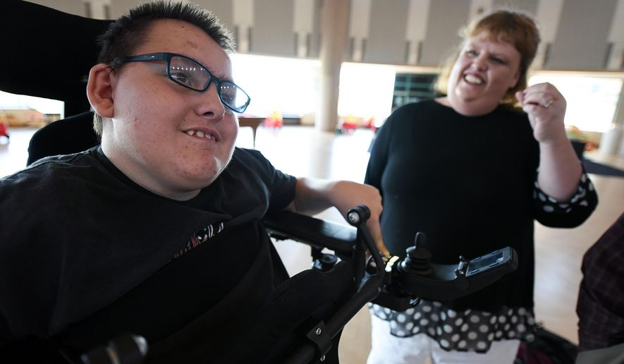 This photo taken Aug. 10, 2016, shows Jacob Hansen, a 16-year-old West High student with cerebral palsy and cystic fibrosis being joined by his mother Jodi, as he is outfitted with a unique motorized wheelchair at Shriner's Hospital in Salt Lake City. The wheelchair allows him to go from a laying position to standing which not only helps his lungs breathe better but reduces strain on his bobby. The federal Education Department's Office for Civil Rights has had students like Jacob in mind this summer when it found that hundreds of state departments of education and school districts across the country had websites that could not be accessed by the deaf, blind, and others who cannot use a computer mouse.    (Francisco Kjolseth/The Salt Lake Tribune via AP)