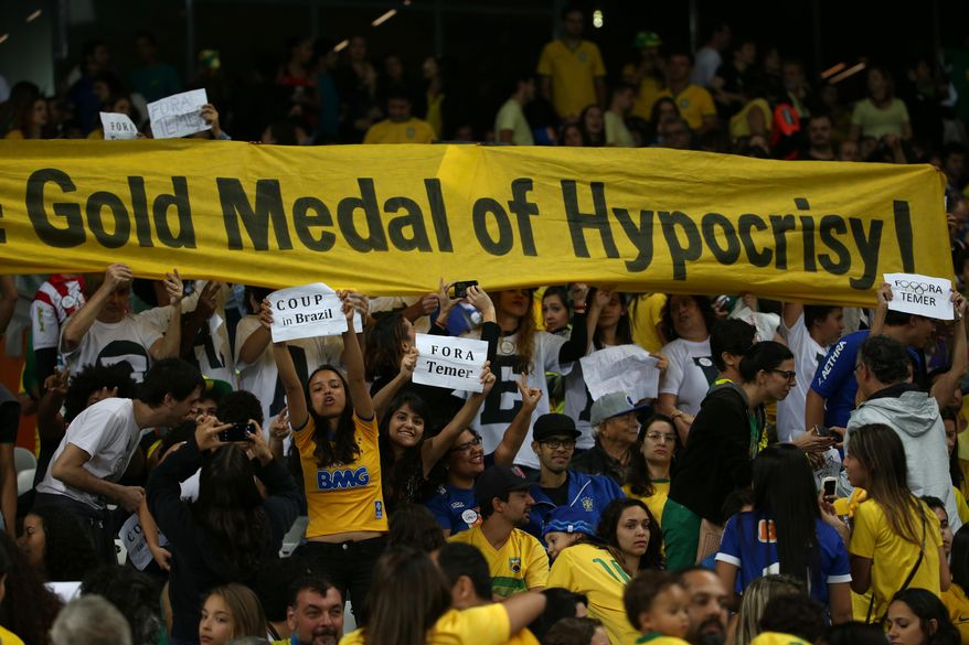 """FILE - In this Aug. 12, 2016 file photo, fans hold signs against interim Brazilian President Michel Temer during a quarter-final match at the women's Olympic football tournament between Brazil and Australia in Belo Horizonte, Brazil. The smaller signs read in Portuguese: """"Coup in Brazil"""" and """"Get out Temer."""" Temer replaced President Dilma Rousseff as interim leader after she was suspended, and both have been at the epicenter of a corruption investigation that has led to the jailing of dozens of politicians and top businessmen. (AP Photo/Eugenio Savio, File)"""