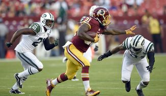 Washington Redskins running back Matt Jones (31) attempts to stiff arm New York Jets cornerback Darrelle Revis (24) during the first half of an NFL preseason football game Friday, Aug. 19, 2016, in Landover, Md. (AP Photo/Nick Wass)