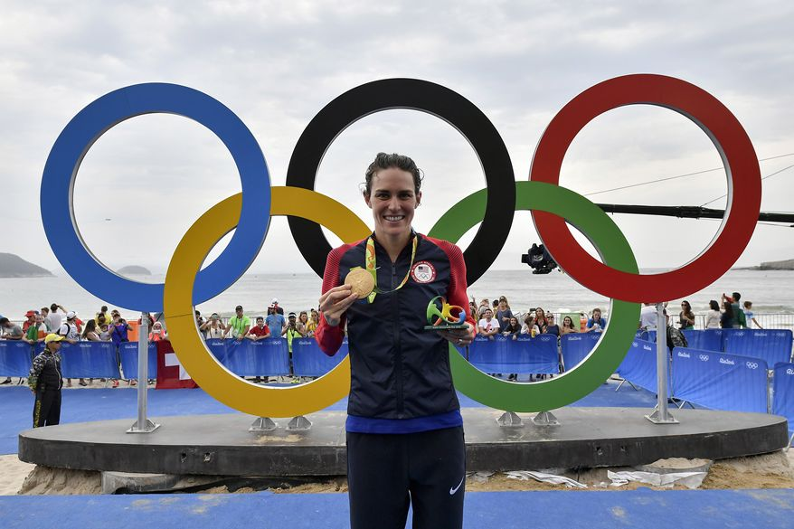 United States' Gwen Jorgensen celebrates with her gold medal next to the Olympic rings after winning the women's triathlon competition of the 2016 Summer Olympics in Rio de Janeiro, Brazil, Saturday, Aug. 20, 2016.   (Jeff Pachoud /Pool Photo via AP) ** FILE **