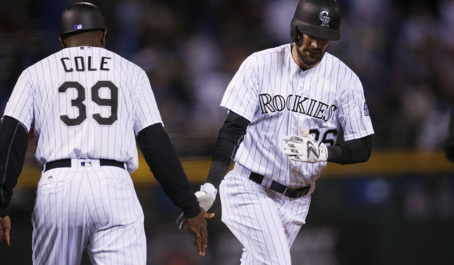Colorado Rockies' David Dahl, left, is congratulated by third base coach Stu Cole while circling the bases after hitting a solo home run off Chicago Cubs starting pitcher Kyle Hendricks in the first inning of a baseball game Friday, Aug. 19, 2016, in Denver. (AP Photo/David Zalubowski)