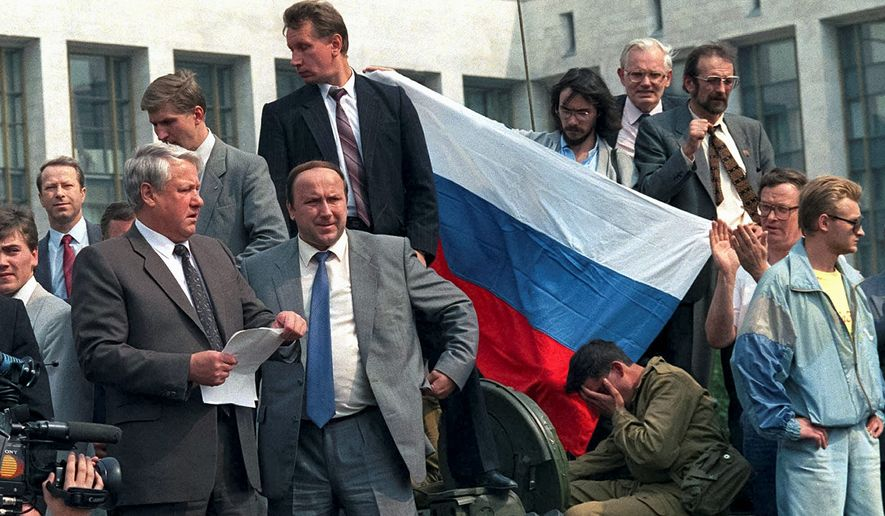 On Aug. 19, 1991, bodyguards surround Boris Yeltsin (left) as he addresses a crowd from atop of a tank in front of the Russian Government building, also known as White House. (Associated Press)