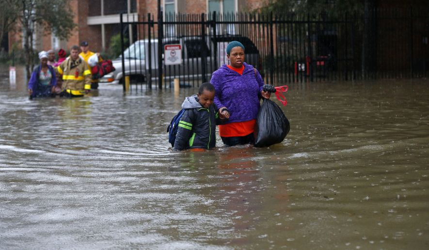 Residents wade through floodwaters from heavy rains in the Chateau Wein Apartments in Baton Rouge, La., on Aug. 12. (Associated Press)