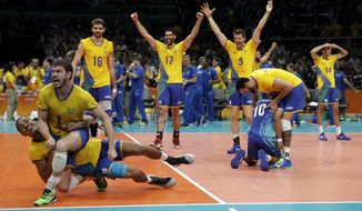 Members of Brazil's team celebrates a win after a men's gold medal volleyball match against Italy at the 2016 Summer Olympics in Rio de Janeiro, Brazil, Sunday, Aug. 21, 2016. (AP Photo/Matt Rourke)