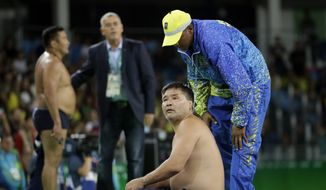 Coaches for Mongolia's Mandakhnaran Ganzorig strip in protest after a loss to Uzbekistan's Ikhtiyor Navruzov during the men's 65-kg freestyle bronze medal wrestling match at the 2016 Summer Olympics in Rio de Janeiro, Brazil, Sunday, Aug. 21, 2016. (AP Photo/Marcio Jose Sanchez)