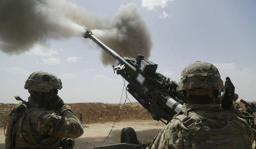 In this file photo, U.S. Army soldiers with 1st Battalion, 320th Field Artillery Regiment, 2nd Brigade Combat Team, 101st Airborne Division (Air Assault), fire an M777 howitzer at Kara Soar Base, Iraq. In March 2021 the 4th Battalion, 319th Artillery Regiment, part of the 173rd Airborne Brigade, will train in France with French-made anti-tank rounds. (Associated Press) **FILE**