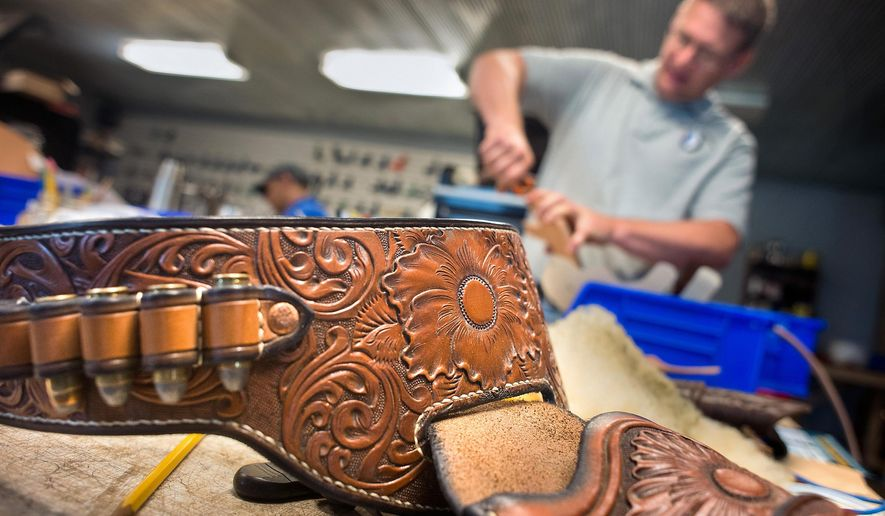 ADVANCE FOR USE SUNDAY, AUG. 21 - In this July 19, 2016 photo, Mark Fedders of Lobo Gun Leather, works in the shop in front of a bullet belt outside Orange City, Iowa. (Justin Wan/Sioux City Journal via AP)