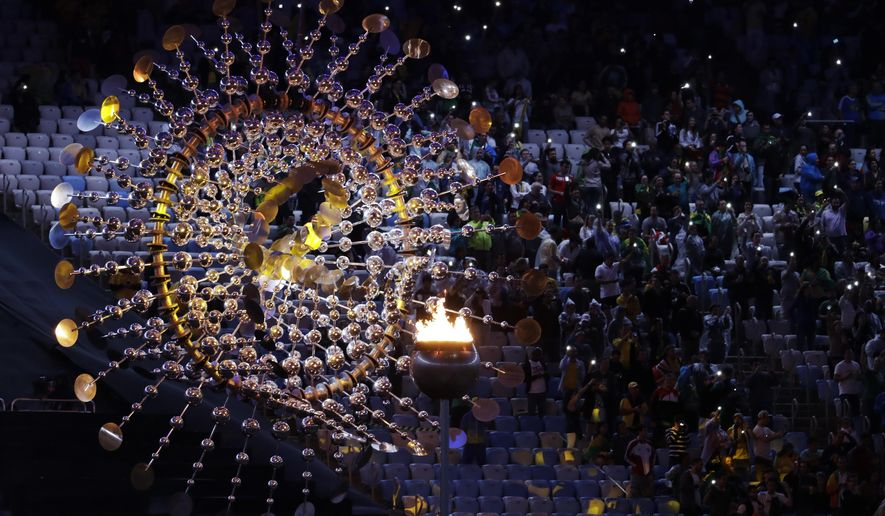 Spectators sit beside the cauldron with the Olympic flame prior to the closing ceremony in the Maracana stadium at the 2016 Summer Olympics in Rio de Janeiro, Brazil, Sunday, Aug. 21, 2016. (AP Photo/Natacha Pisarenko)