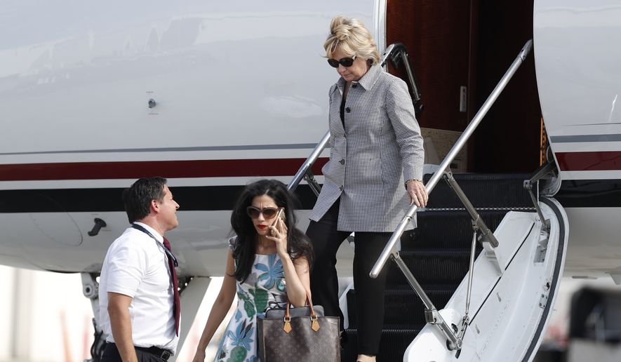 "Democratic presidential nominee Hillary Clinton and aide Huma Abedin, lower left on cell phone, step from Clinton's campaign plane as they arrive at Van Nuys Airport in Van Nuys, Calif., Monday, Aug. 22, 2016, en route to a taping of ""Jimmy Kimmel Live!"" in Los Angeles. (AP Photo/Carolyn Kaster)"