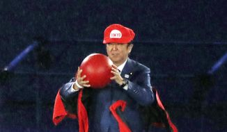 Japanese Prime Minister Shinzo Abe removes costume of the Nintendo game character Super Mario as he makes an appearance during the closing ceremony at the 2016 Summer Olympics in Rio de Janeiro, Brazil, Sunday, Aug. 21, 2016. Abe's brief but show-stopping appearance as Super Mario offered a tantalizing glimpse at Tokyo's plans for the 2020 games. (Masanori Takei/Kyodo News via AP)