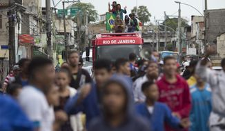 "Brazilian judo gold medalist Rafaela Silva is given a hero's welcome as she rides a fire truck into the Cidade de Deus ""City of God"" slum in Rio de Janeiro, Brazil, Monday, Aug. 22, 2016. Silva who grew up in the violent, poverty stricken slum, won special mention from IOC president Thomas Bach, saying she's an inspiration across the world."" (AP Photo/Leo Correa)"