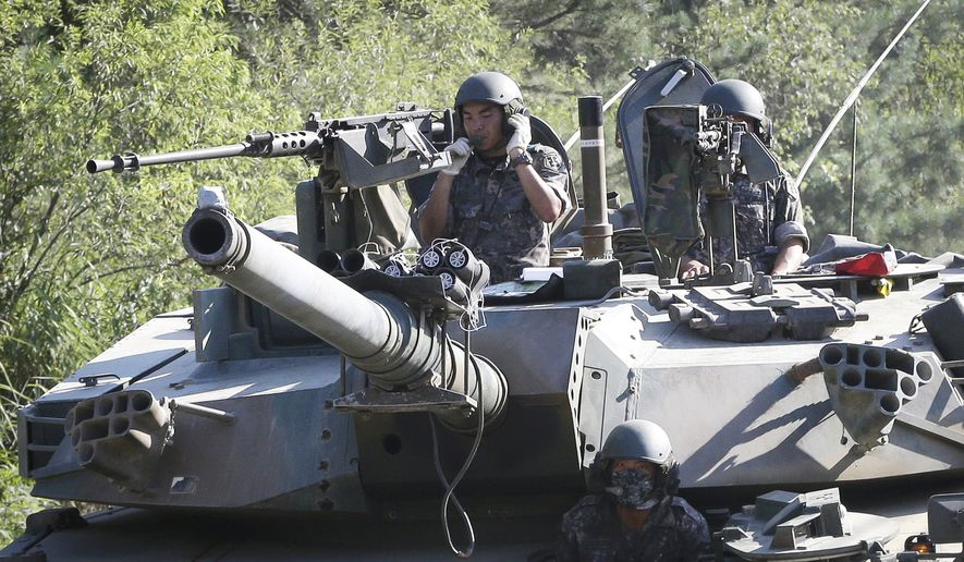 South Korean army soldiers ride a K-1 tank during the annual exercise in Paju, South Korea, near the border with North Korea, Monday, Aug. 22, 2016. South Korea and the United States began annual military drills Monday despite North Korea's threat of nuclear strikes in response to the exercises that it calls an invasion rehearsal. (AP Photo/Ahn Young-joon)