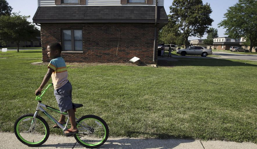 In this Wednesday, Aug. 3, 2016 photo, a child rides his bicycle past the West Calumet Housing Complex in East Chicago, Ind. More than 1,000 residents of a public housing complex in northwest Indiana have been left in a state of panic and uncertainty since authorities informed them last month that their homes need to be destroyed because of a serious lead contamination threat. (Jonathan Miano/The Times via AP)