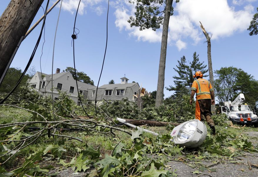 A tree removal worker walks past a downed light pole and lines, Monday, Aug., 22, 2016, in Concord, Mass. A tornado briefly touched down in the historic Massachusetts town, uprooting trees, knocking out power, and causing damage to dozens of homes. There were no reports of injuries. (AP Photo/Elise Amendola)