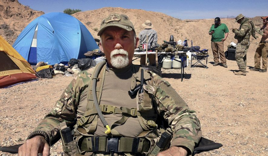 FILE - In this April 16, 2014 file photo, Jerry DeLemus, of Rochester, N.H., sits with a group of self-described militia members camping on rancher Cliven Bundy's ranch near Bunkerville, Nev. Delemus one of two defendants are set to become the first to plead guilty  Tuesday, Aug. 23, 2016, in Nevada to federal charges stemming from an armed confrontation with U.S. land management agents near Nevada rancher Cliven Bundy's ranch in 2014.  (AP Photo/Ken Ritter, File)