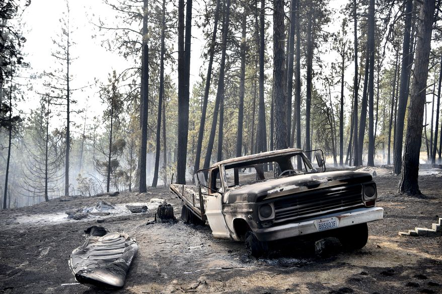 A charred truck is seen near the home of Julie Thayer and her husband, Art, on South Yale Road near Valleyford, Wash., on Monday, Aug 22, 2016. The Thayers had been hiking over the weekend and returned home Sunday night to find their home destroyed. (Tyler Tjomsland/The Spokesman-Review via AP)