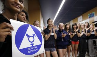 Deena Kennedy holds a sticker for a new gender neutral bathroom as members of the cheer squad applaud behind during a ceremonial opening for the restroom at Nathan Hale high school in Seattle on May 17, 2016. (Associated Press)