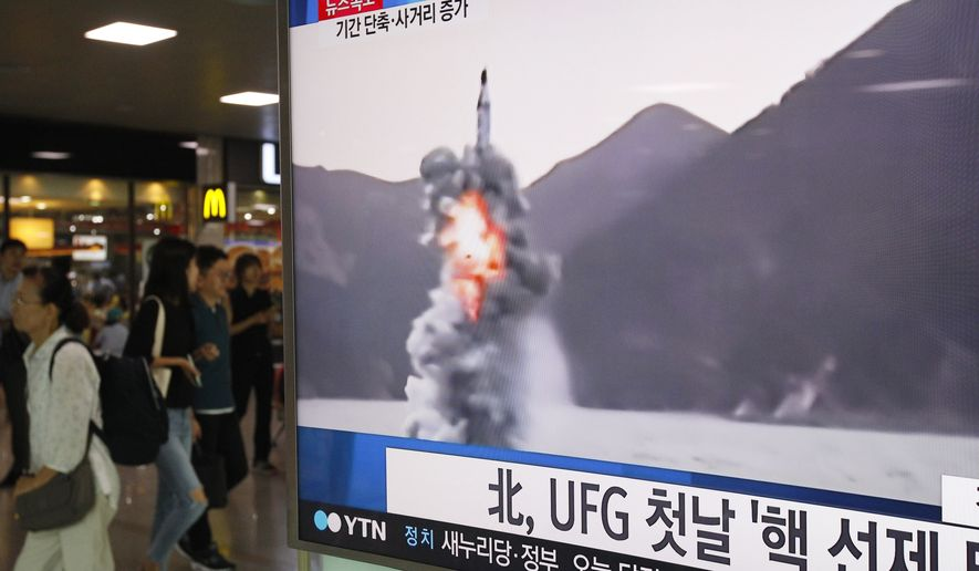 """People pass by a TV news program showing a file footage of North Korea's ballistic missile that the North claimed to have launched from underwater, at Seoul Railway station in Seoul, South Korea, Wednesday, Aug. 24, 2016. North Korea on Wednesday fired a ballistic missile from a submarine into the sea in an apparent protest against the start of annual South Korea-U.S. military drills, Seoul's military said. The letters read """"North Korea fired a missile during UFG, Ulchi Freedom Guardian."""" (AP Photo/Ahn Young-joon)"""