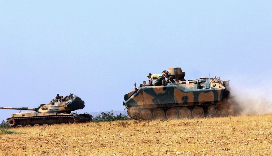 A Turkish army tank and an armored vehicle are stationed near the border with Syria, in Karkamis, Turkey, Tuesday, Aug. 23, 2016. Turkish media reports say Turkish artillery on Tuesday launched new strikes at Islamic State targets across the border in Syria, after two mortar rounds, believed to have been fired by the militants, hit the town of Karkamis, in Turkey's Gaziantep province. Hurriyet newspaper and other reports said the mortar rounds were fired from IS-held Jarablus, Syria.(IHA via AP)
