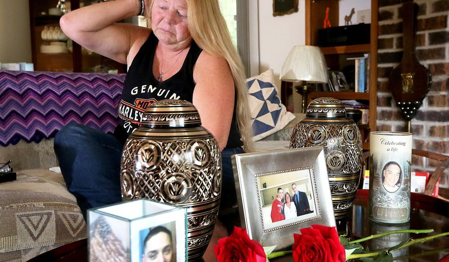In this Aug. 11, 2016 photo, Sherri Smith reflects on the loss of her adult twin sons, Jesse and Tony Sparks, who both died of apparent drug overdoses in Madison, Wis.. Tony passed away in 2005 at age 25, and Jesse in July at age 34. A small memorial to the men, including the urns containing their ashes, is displayed on a table at her mother's home. (John Hart/Wisconsin State Journal via AP)