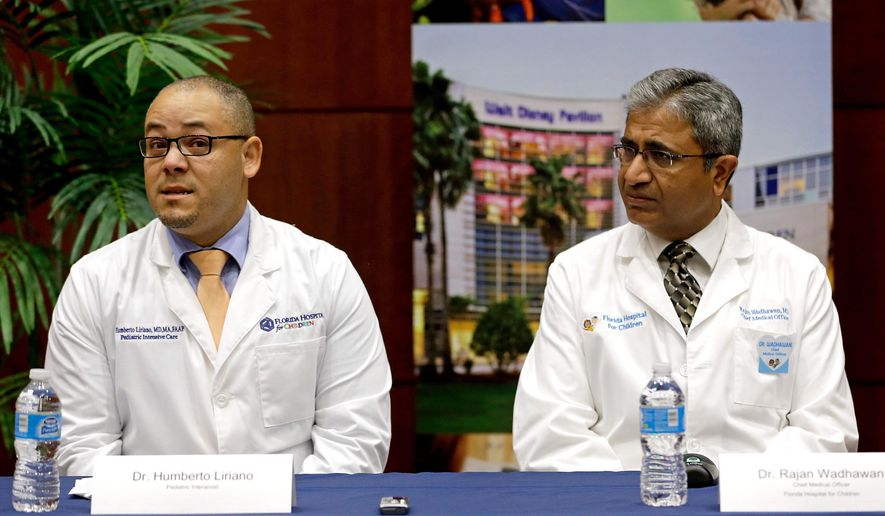 Dr. Humberto Liraino, left, makes comments during a news conference as Dr. Rajan Wadhawan listens, at Florida Hospital, Tuesday, Aug. 23, 2016, in Orlando, Fla. The doctor spoke about the treatment of Sebastian DeLeon, a patient that has survived a brain-eating amoeba that kills most people who contract it. (AP Photo/John Raoux)