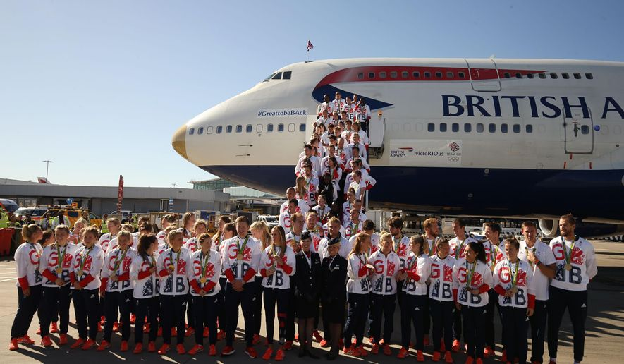 Members of the GB squad form a group as they arrive at London's Heathrow Airport, Tuesday Aug. 23, 2016, on their return from the 2016 Olympics in Rio de Janeiro. Team GB arrive back in the United Kingdom after finishing second in the Rio 2016 Olympic medal table, surpassing their London 2012 medal haul with a total of 67 medals. (Steve Parsons/PA via AP)