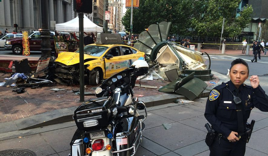 San Francisco Police Officer Grace Gatpandan, right, stands by the scene of a taxi crash in downtown San Francisco Tuesday, Aug. 23, 2016. SFPD Officer Gatpandan says three people are critically injured Tuesday, after a taxi jumped a curb and plowed into an advertising kiosk and a shoe shine stand at a busy corner in downtown San Francisco. The taxi driver and two people who were at the shoe shine stand were rushed to a hospital with life threatening injuries. (AP Photo/Paul J. Elias)