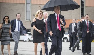 Republican presidential candidate Donald Trump walks in the rain with Florida Attorney General Pam Bondi, as they arrive at a campaign rally in Tampa, Fla., Wednesday, Aug. 24, 2016. (Loren Elliott/Tampa Bay Times via AP) **FILE **