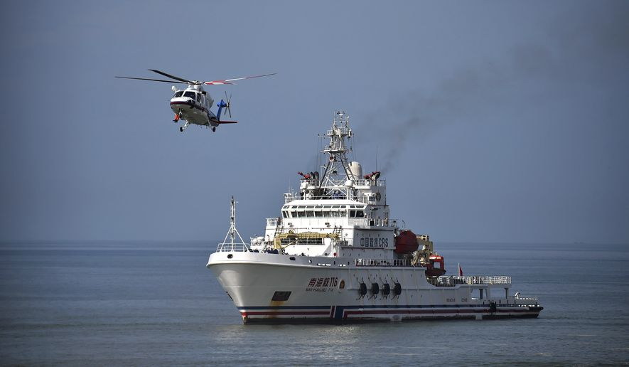 In this photo released by Xinhua News Agency, a rescue helicopter and vessel take past in an emergency rescue drill held on the South China Sea near Fenghuang island in Sanya, southern China's Hainan Province, Aug. 23, 2016. The drill aims at enhancing the emergency response capabilities of maritime rescue teams. (Guo Cheng/Xinhua via AP)